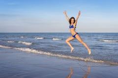 Ung gladlynt kvinna i bikinibanhoppning på stranden royaltyfri fotografi