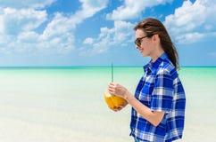 Ung gladlynt kvinna med kokosnöten mot turkoshavet arkivfoto