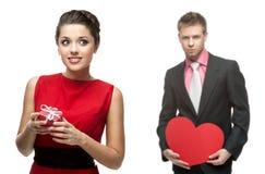 Ung gladlynt kvinna och stilig man som rymmer röd hjärta på vit Fotografering för Bildbyråer