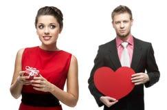 Ung gladlynt kvinna och stilig man som rymmer röd hjärta på vit Royaltyfri Bild
