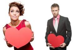 Ung gladlynt kvinna och stilig man som rymmer röd hjärta på vit Royaltyfria Bilder