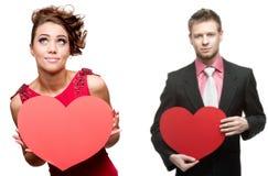 Ung gladlynt kvinna och stilig man som rymmer röd hjärta på vit Arkivfoto