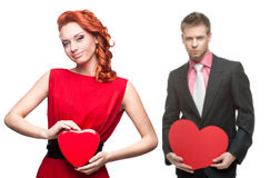 Ung gladlynt kvinna och stilig man som rymmer röd hjärta på vit Royaltyfri Fotografi
