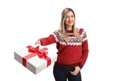 Ung gladlynt kvinna som bär en röd tröja och rymmer en gåva royaltyfri fotografi