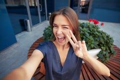 Ung gladlynt kvinna som visar tecken V och blinkar, medan göra ett s Fotografering för Bildbyråer