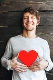 Ung gladlynt le man som rymmer det röda hjärtatecknet Royaltyfri Bild