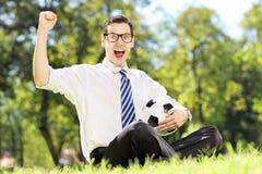 Ung gladlynt man som rymmer en boll och gör en gest lycka Arkivbilder