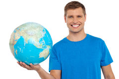 Ung gladlynt man som rymmer ett jordklot i hans hand Arkivfoto