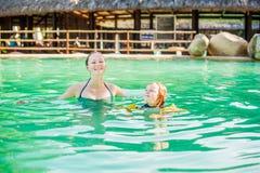 Ung gladlynt moder och son i en simbassäng arkivbilder