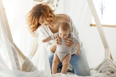 Ung gladlynt moder som skrattar och spelar med den nyfödda gulliga sonen i hemtrevligt ljust sovrum i morgon Atmosfär av lyckligt Fotografering för Bildbyråer