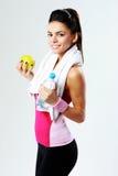 Ung gladlynt sportkvinna med äpplet och flaskan av vatten Fotografering för Bildbyråer
