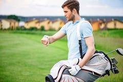 Ung golfare som kontrollerar tid på smartwatch Arkivfoto