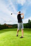 Ung golfspelare på kursen som gör golfswing Royaltyfria Bilder