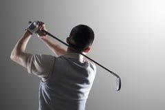 Ung golfspelare som svänger, bakre sikt Fotografering för Bildbyråer