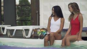 Ung grabb i bad för simningstammar till två härliga flickor i baddräkter som har gyckel på pölen Vänner spenderar fritid stock video