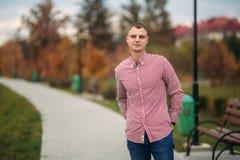 Ung grabb i rött skjortastag i parkera arkivfoto