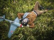 Ung grabb i tappningkläderpilot med en flygplanmodelloutdoo Arkivfoton