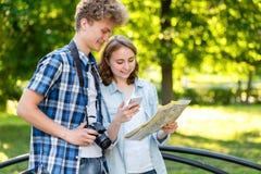 Ung grabb med en flicka I sommaren i staden i natur Turister rymmer en färdplan I händer av en smart telefon royaltyfria foton
