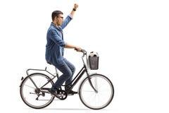 Ung grabb med en fotboll som rider en cykel och gör en gest lycka Arkivfoto