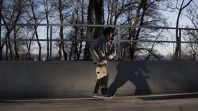 Ung grabb - skateboradåkareutbildning som är utomhus- i stadsskridsko, parkera - skateboarding för ung man med longboard i stads- stock video