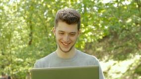 Ung grabb som arbetar med bärbara datorn och att skratta