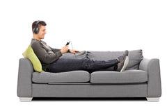 Ung grabb som ligger på soffan och lyssnar till musik Royaltyfria Bilder