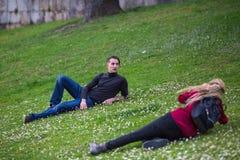 Ung grabb som poserar för en kvinnlig fotograf som ligger i ängen Arkivfoton