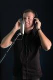 Ung grabb som sjunger i studiomikrofonen royaltyfri bild
