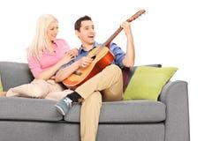 Ung grabb som spelar gitarren med hans flickvän Arkivbilder
