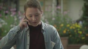 Ung grabb som talar på telefonen på en stadsgata stock video