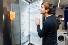 Ung grabb som väljer det inhemska kylskåpet royaltyfria foton