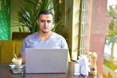 Ung grabbfreelancer som arbetar på bärbara datorn i kafé uppmärksam focuse för man arkivbilder