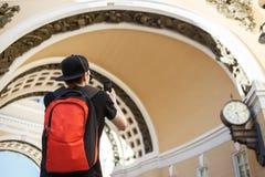 Ung grabbturist med ryggsäcken som fotograferar den historiska bågen av byggnad för allmän personal i slottfyrkanten i St Royaltyfria Foton