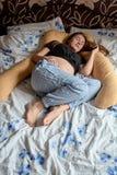 Ung gravid kvinna Den gravida h?rliga kvinnan sover p? moderskapkudden i s?ng arkivfoto