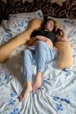 Ung gravid kvinna Den gravida h?rliga kvinnan sover p? moderskapkudden i s?ng arkivbild