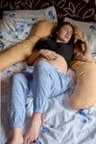 Ung gravid kvinna Den gravida h?rliga kvinnan sover p? moderskapkudden i s?ng royaltyfria bilder