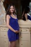 Ung gravid kvinna i den violetta klänningen Arkivfoto