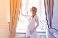 Ung gravid kvinna i den vita klänningen Royaltyfri Fotografi