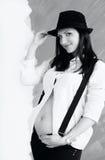 Ung gravid kvinna i den vita skjortan med hängslen och hatten Royaltyfri Bild