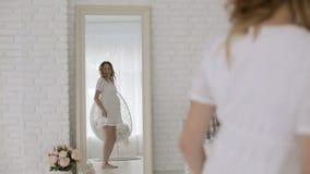 Ung gravid kvinna i en vit klänning som har rolig dans framme av en spegel lager videofilmer