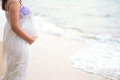 Ung gravid kvinna i klänninginnehavhänder på buken på suddigt royaltyfria foton