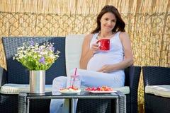 Ung gravid kvinna och att ha den sunda frukosten i trädgård Arkivfoton