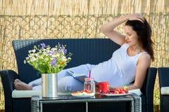 Ung gravid kvinna och att ha den sunda frukosten i trädgård Royaltyfri Bild