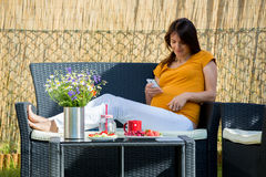 Ung gravid kvinna och att ha den sunda frukosten i trädgård Royaltyfri Foto