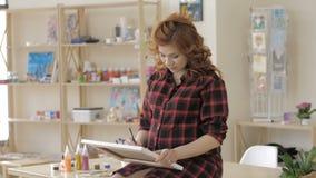 Ung gravid kvinna som drar m?lning i konststudio, sunt lyckligt livsstilbegrepp arkivfilmer