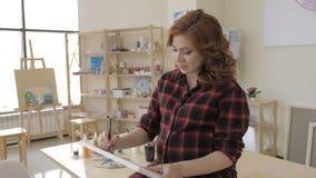 Ung gravid kvinna som drar m?lning i konststudio, sunt lyckligt livsstilbegrepp lager videofilmer