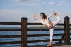 Ung gravid kvinna som gör yoga vid floden Royaltyfria Bilder
