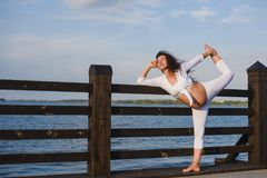 Ung gravid kvinna som gör yoga vid floden Fotografering för Bildbyråer