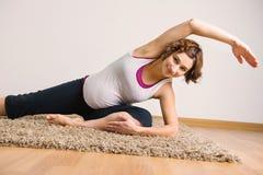 Ung gravid kvinna som gör yogaexecises fotografering för bildbyråer