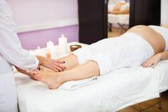 Ung gravid kvinna som kopplar av med handbenmassage på skönhetsp fotografering för bildbyråer